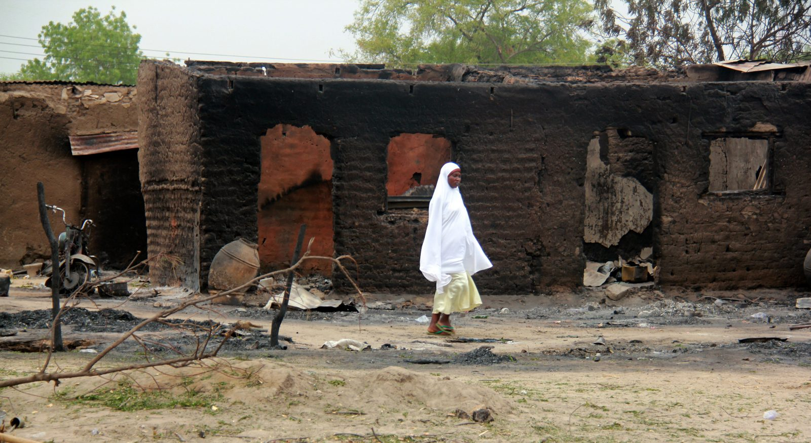 woman walking past burnt houses